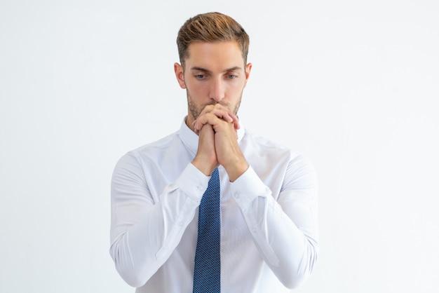 Homme d'affaires pensif, pensant fort avec ses mains jointes