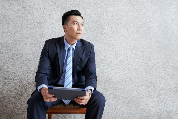 Homme d'affaires pensif avec tablette