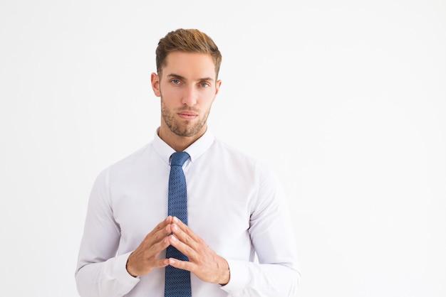 Homme d'affaires pensif tenant les mains ensemble