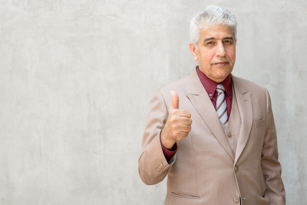 Homme d'affaires persan mature aux cheveux gris donnant les pouces contre le mur de béton à l'extérieur