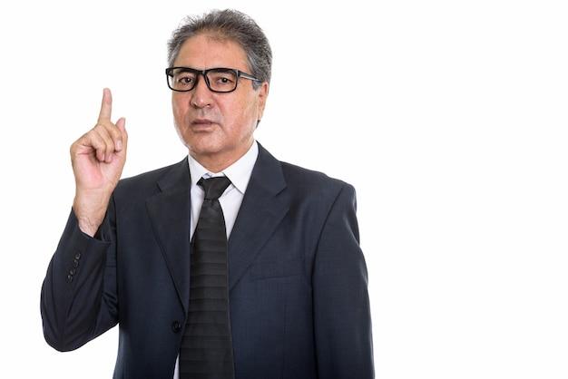 Homme d'affaires persan senior portant des lunettes et pointant vers le haut