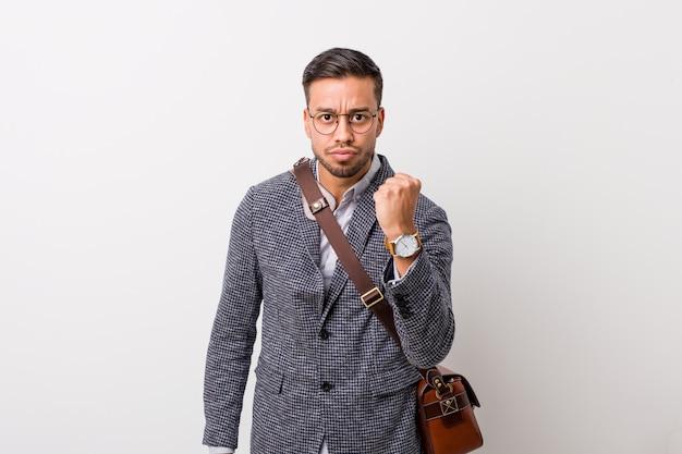 Homme d'affaires philippin de jeunes entrepreneurs contre un mur blanc montrant le poing à la caméra, expression faciale agressive.