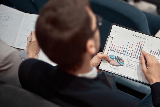 Homme d'affaires de plan rapproché avec un programme financier se reposant dans une salle de conférence