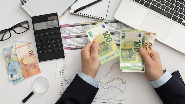 Homme d'affaires plat laïc vérifiant les manières de la finance
