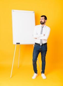 Homme d'affaires pleine longueur donnant une présentation sur tableau blanc sur un mur jaune isolé avec une expression du visage confuse