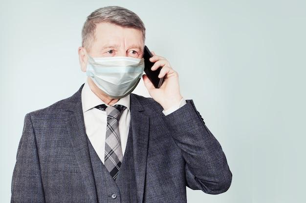 Homme d'affaires plus âgé, parler au téléphone et porter un masque