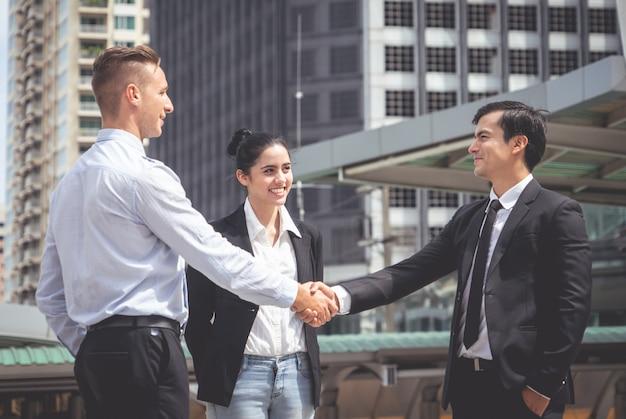 Homme d'affaires avec poignée de main avec partenaire et femme acclamant