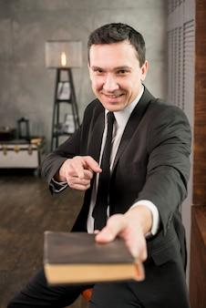 Homme d'affaires pointant à la caméra et recommandant le livre
