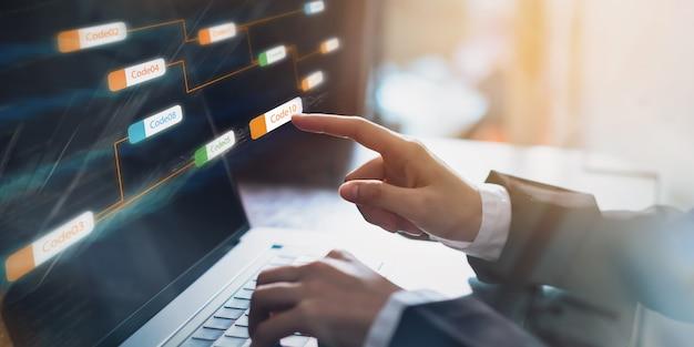 Homme d'affaires pointant le code icône icône cohérent et écran de développement d'applications sur l'ordinateur portable.