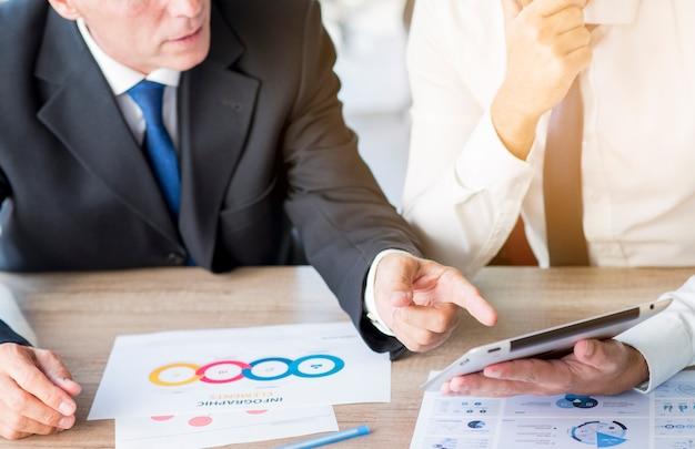Homme d'affaires, pointant le doigt sur la tablette numérique tenue par son partenaire sur le lieu de travail
