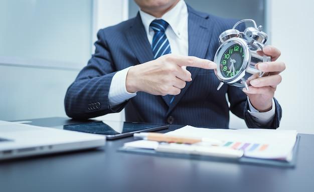 Homme d'affaires pointant sur l'horloge. photo gros plan
