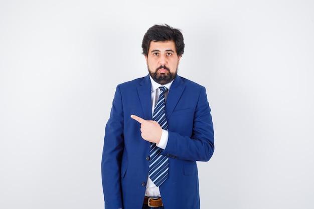 Homme d'affaires pointant vers la gauche avec l'index en costume formel et semblant sérieux, vue de face.