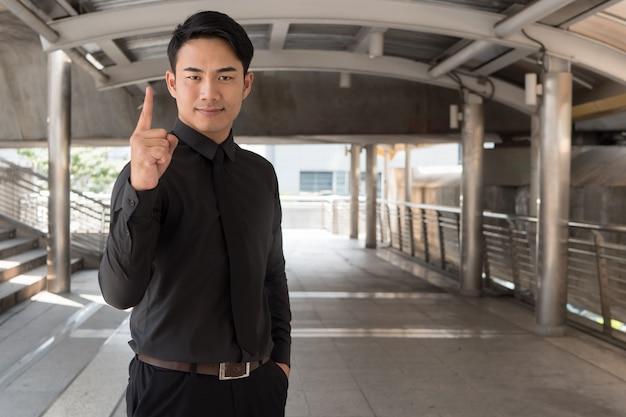 Homme d'affaires pointant vers le haut le geste de la main du doigt numéro 1