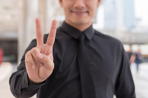 Homme d'affaires pointant vers le haut le geste de la main du doigt numéro 2, signe v victoire