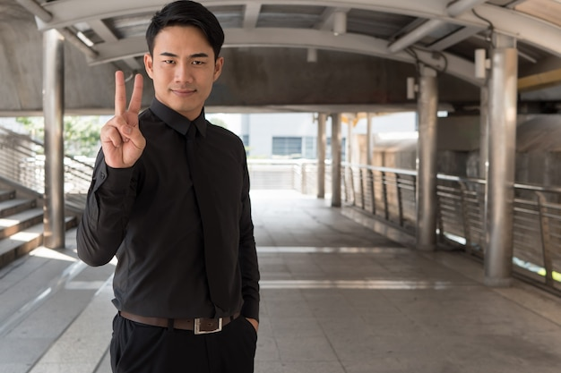 Homme d'affaires pointant vers le haut le geste de la main du doigt numéro 2