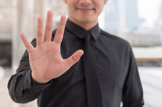 Homme d'affaires pointant vers le haut le geste de la main du doigt numéro 5