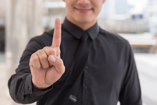 Homme d'affaires pointant vers le haut le geste de la main du doigt numéro