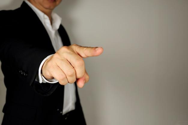Homme d'affaires pointe son doigt sur fond gris