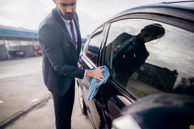 Homme d'affaires polissant sa voiture avec un chiffon en microfibre devant le lave-auto.