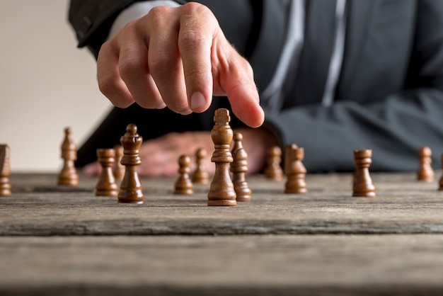 Homme d'affaires portant un costume d'affaires jouant aux échecs sur une vieille table en bois dans une vue rapprochée de sa main atteignant la pièce du roi noir.