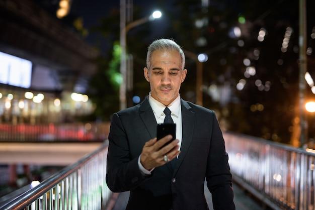 Homme d'affaires portant un costume dans la ville pendant la nuit tout en utilisant un téléphone mobile