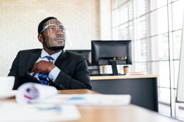 Homme d & # 39; affaires portant un écran facial écoute et partage son opinion
