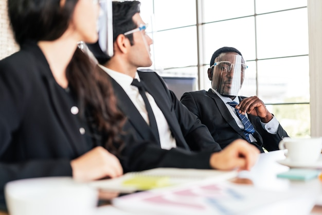 Homme d & # 39; affaires portant un écran facial en regardant ses collègues