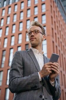 Homme d'affaires portant des lunettes utilisant la communication par téléphone mobile en ligne regardant loin dans la rue