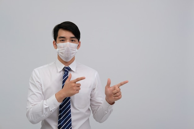 Homme d'affaires portant un masque de protection et pointant