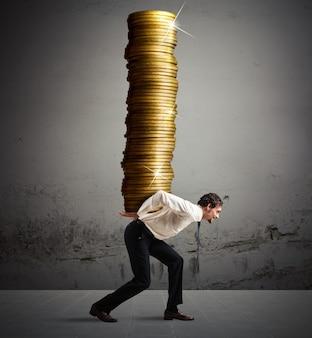 Homme d'affaires porte sur son dos une pile de pièces de monnaie
