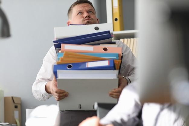 Homme d'affaires porte un tas de dossiers