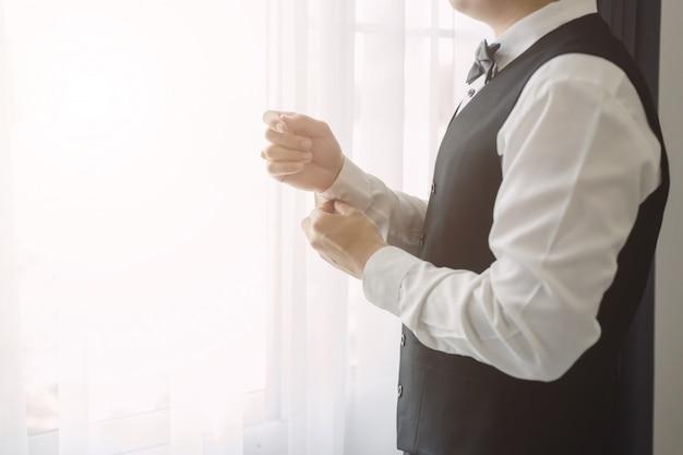 Homme d'affaires porter le bouton de manchette bouchent