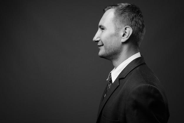 Homme affaires, porter, costume, contre, mur gris, dans, noir blanc