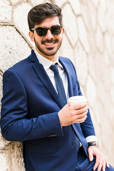 Homme d'affaires posant avec un café