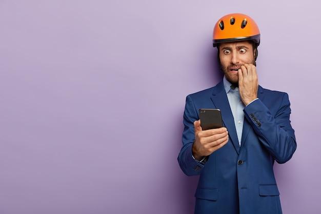 Homme d & # 39; affaires posant en costume élégant et casque rouge au bureau