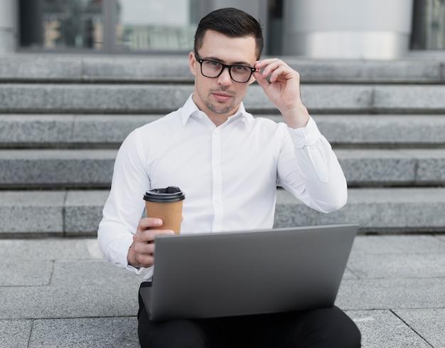 Homme d'affaires posant avec des lunettes