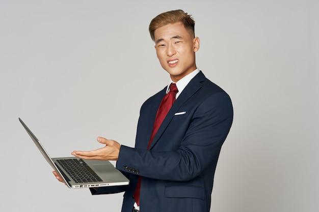 Homme d & # 39; affaires posant tenant un ordinateur portable