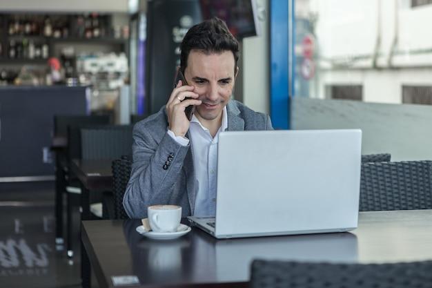 Homme d'affaires positif avec ordinateur portable, parler au téléphone au café