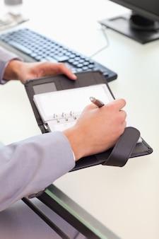Homme d'affaires prenant des notes sur son calendrier de poche