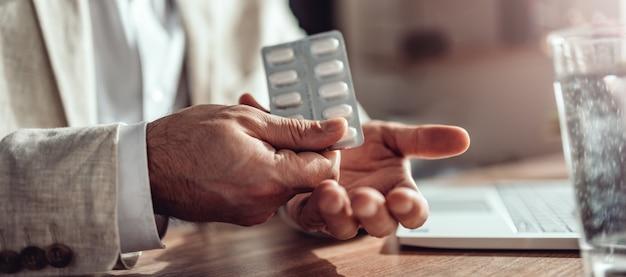 Homme d'affaires prenant des pilules médicales au bureau