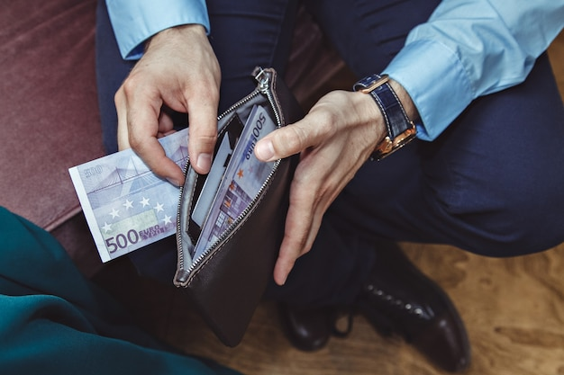 L'homme d'affaires prend de l'argent de son portefeuille en cuir
