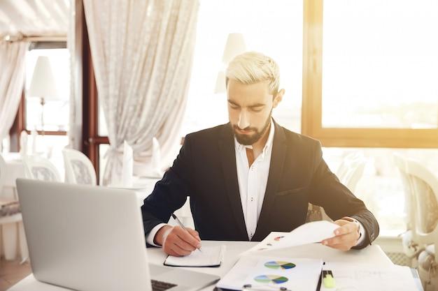 Homme d'affaires prend des notes à partir de l'analyse du diagramme dans la salle de conférence