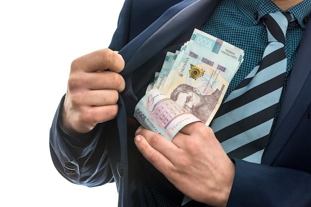 L'homme d'affaires prend un paquet d'argent ukrainien comme pot-de-vin et se cache dans sa poche dans une veste