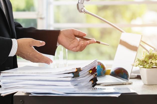 Homme d'affaires préparer des rapports avec des graphiques, des tableaux sur des piles de fichiers pour la finance