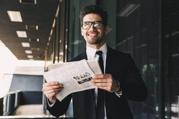 Homme d'affaires près du centre d'affaires tenant la lecture du journal.