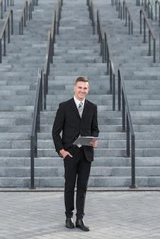 Homme affaires, presse-papiers, devant, escalier