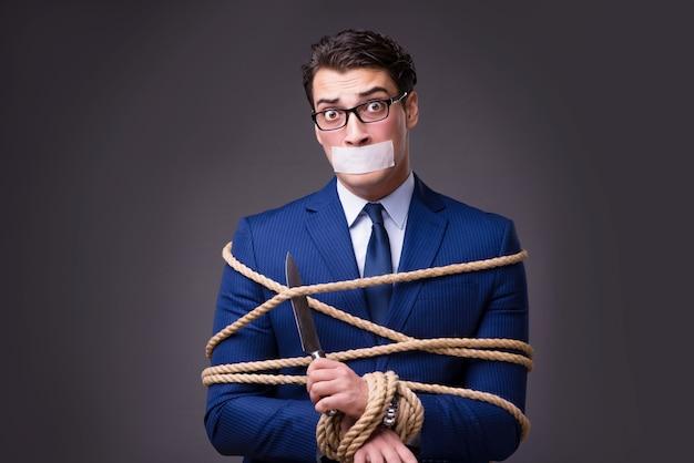 Homme d'affaires pris en otage et ligoté avec une corde