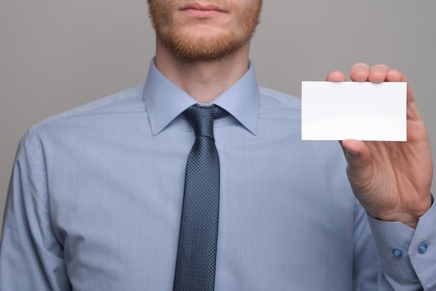 Homme d'affaires, prise de main de l'homme d'affaires montrant la carte de visite - gros plan sur fond gris. montrez une feuille de papier vierge. carte de visite papier.