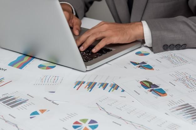 Homme d'affaires professionnel avec la technologie de l'ordinateur portable et des données graphiques financières aux entreprises
