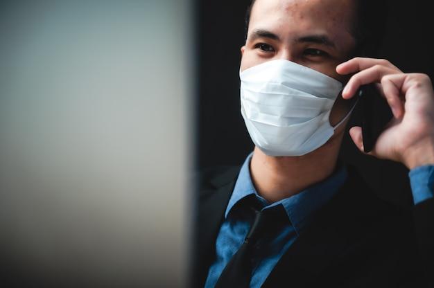 Homme d'affaires professionnel travaillant avec un laboratoire informatique pendant la quarantaine à domicile de la pandémie de virus corona grippe via un masque chirurgical